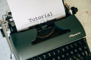 green and black typewriter with white printer paper